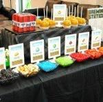 Eight snack items arranged in a colorful manner with signs depicting items found in in the Minecraft world. Food items include: chocolates, rock candy, fruit and vegetables.